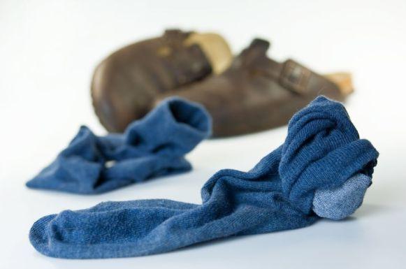 7626553 - blaue, getragene socken und hausschuhe liegen auf dem boden